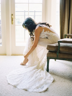 Bride in beaded wedding dress illusion low back putting on heels train armchair