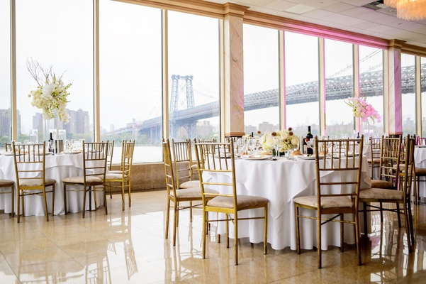 Wedding reception in Brooklyn with view of east river and famous bridges white linens gold chairs