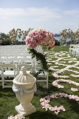 Stone urn sculpture and pink rose arrangement at aisle