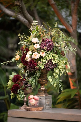 wedding reception wood bar with bowl of peaches and centerpiece with greenery burgundy flowers
