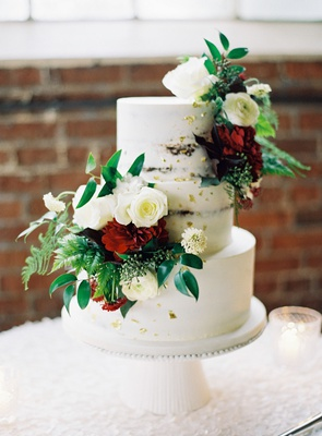 wedding reception brick wall cake stand white three layer cake with greenery white rose red flower