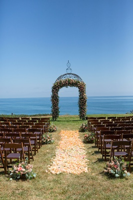 Wedding ceremony on grass lawn overlooking Pacific Ocean flower petal aisle wood chairs small flower
