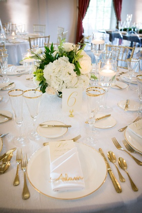 Wedding reception table white linen gold white charger gold flatware white low centerpiece glasses