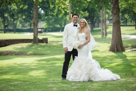 Bride in Vera Wang ruffle mermaid wedding dress and groom on lawn