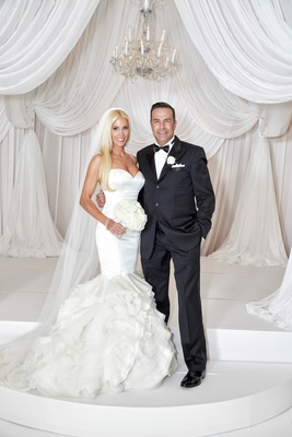 bride in rivini ruffled mermaid wedding dress, groom in tux, all white decor