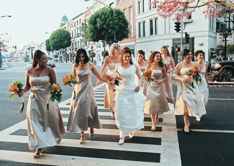Neutral bridesmaid dresses and orange flowers
