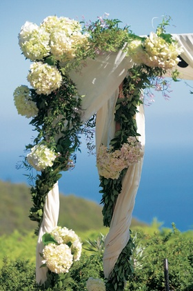 White flowers and greenery on ceremony canopy