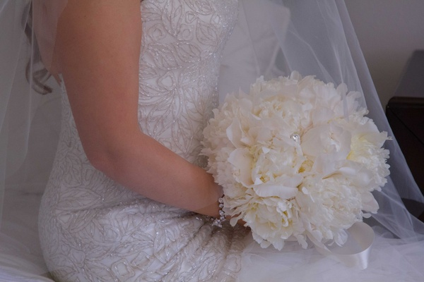 Bride in embroidered gown holding white peony flower bouquet with ribbon on stems