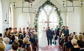 wedding ceremony bride and groom altar cross arch window greenery flower petals wood floor pews