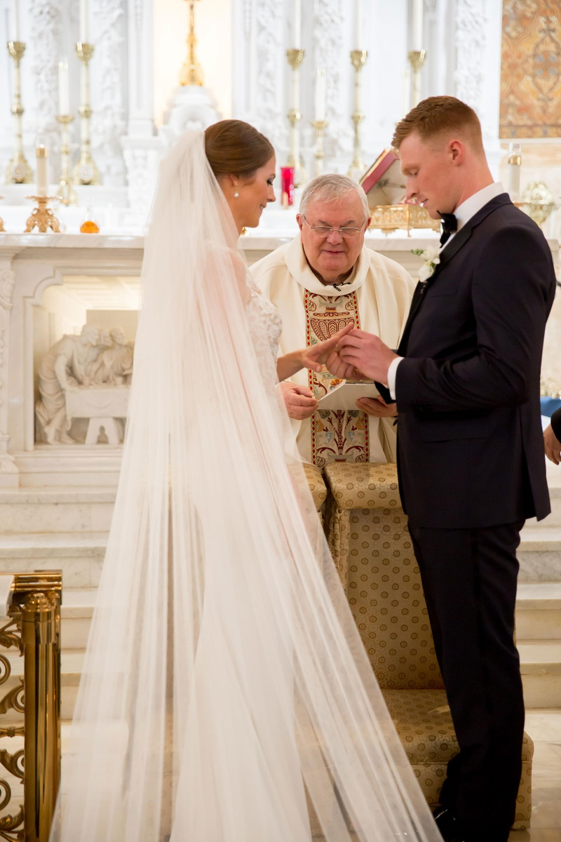 bride and groom exchanging rings during roman catholic wedding ceremony
