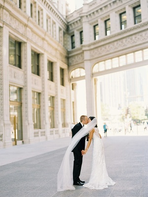 Bride in lace wedding dress with long veil kisses groom in Chicago courtyard tuxedo bow tie