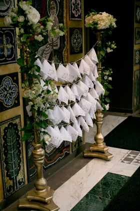 Wedding ceremony at Greek Orthodox church with rows of white handkerchiefs on gold stand clothespin