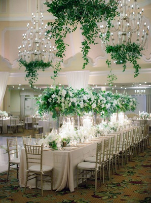 wedding reception ballroom long table gold chair tall green centerpiece white flowers chandeliers