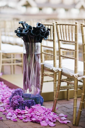 Wedding ceremony gold chairs white cushions fuchsia flower petals purple calla lilies in tall vase