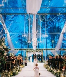 wedding ceremony winter blue outdoor clear tent white drapery chandelier lights greenery gold runner