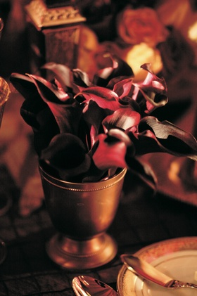 Wedding reception table is decorated with red calla lilies in a small golden vase