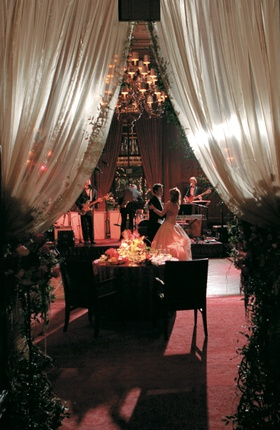 Bride and groom dance under drapery and chandelier