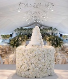 white wedding cake with fresh flower decorations on flower cake table white tent stage