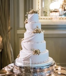 five-tiered wedding cake with fondant drapery and rope accents with golden flowers