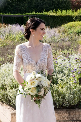 bride in lace v neck carolina herrera gown holds ivory bouquet with greenery