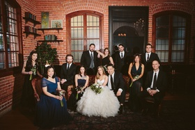 Bride and groom with wedding party in brick building