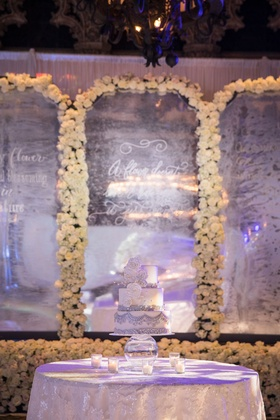 Wedding cake on cake table silver white in front of flower wall mirror quote etched white flowers
