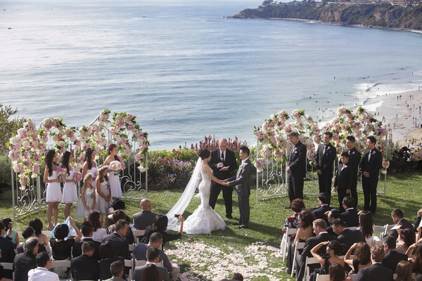 Bride and groom at oceanfront ceremony in front of white gates