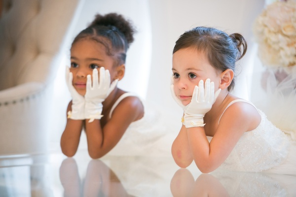 adorable flower girls with white gloves and hands on faces