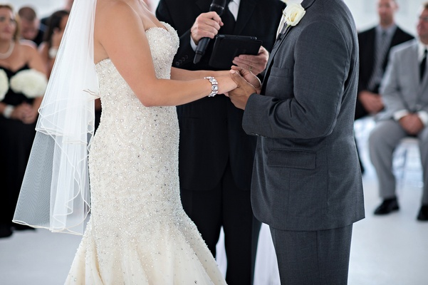 Bride wearing crystal bracelet next to groom at ceremony