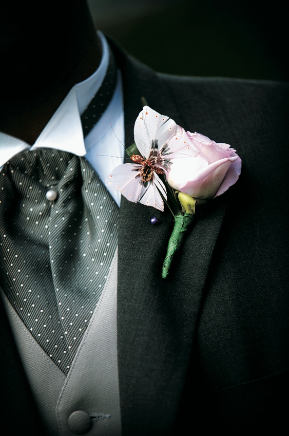 Boutonniere for wedding has a pink rose and butterfly