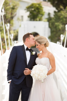 Groom in navy tuxedo with bow tie kissing bride with strapless wedding dress and white bouquet