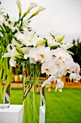 Large vases filled with white lilies and orchids