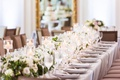 wedding reception table light grey linens flower runner candles in glass votives