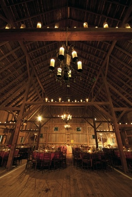 Barn wedding chandelier and candles on rafters