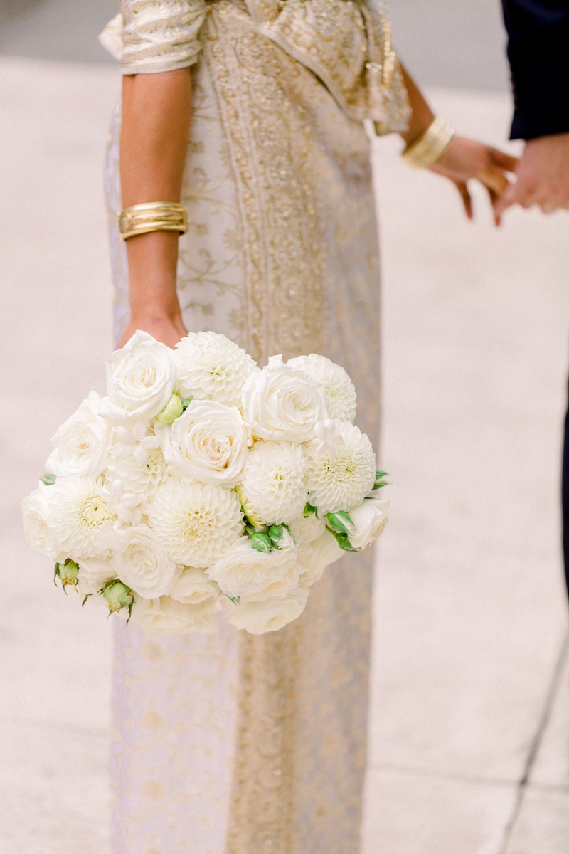 bridal bouquet with ivory roses and dahlias carried by south asian bride in sari