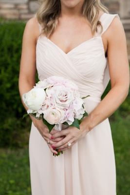 a bridesmaids in a light blush dress holds a bouquets of ivory and blush rose peony ranunculus
