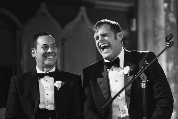 Black and white photo ofMatthew Christopher in a black tuxedo with his groom