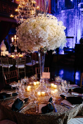 Wedding reception table with a trumpet vase topped with baby's breath and surrounded by candles