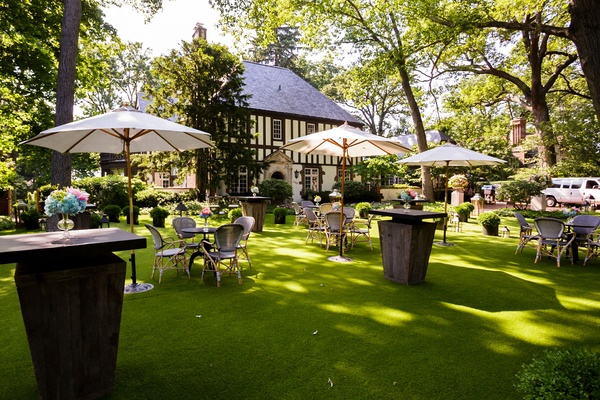 Cocktail hour on grass lawn in backyard of Tudor style home in illinois