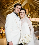 Wedding portrait bride and groom in white white bouquet gold texas emblem in background ceremony