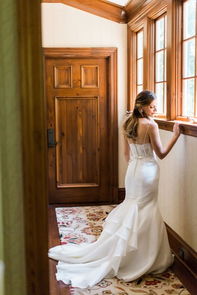 Bride in rustic wedding venue with lace back corset wedding gown and sleek skirt spaghetti straps