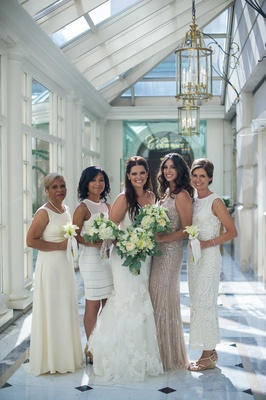 a bride in white trumpet gown bridesmaids different white champagne dresses bouquets foliage
