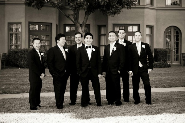 Black and white photo of men in tuxedos outside