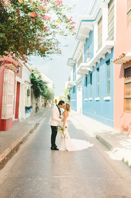 bride and groom portrait streets of colombia colorful houses villas apartments shops white tuxedo