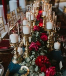 wedding king's table, red floral garland runner, candles on gold stands