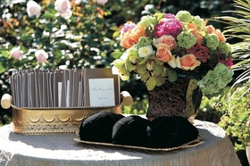Wedding ceremony table holding programs, yarmulkes, and bouquet of green, orange and pink flowers
