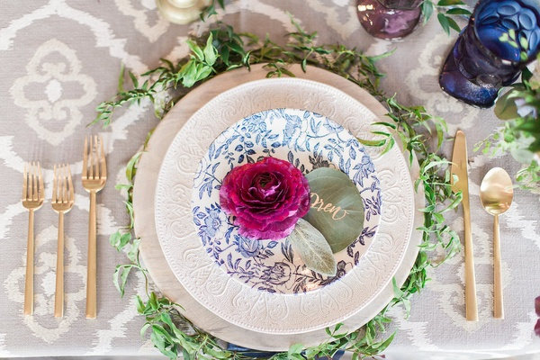 place setting with plum ranunculus blossom and eucalyptus name cards