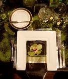 Wedding reception place setting with a square charger, napkin, and orchid