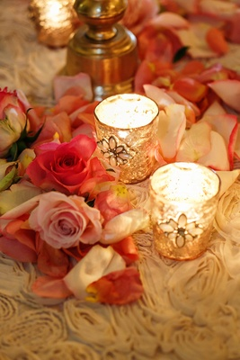 Reception table with pink flower petals and gold candle holders