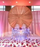Elaborate sweetheart table at Indian wedding drapery, red rose bed